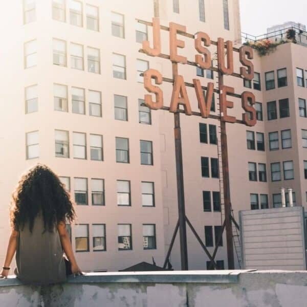 "woman sitting in front of a sign that says ""Jesus Saves"""
