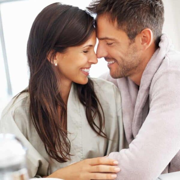 couple facing each other and smiling over coffee