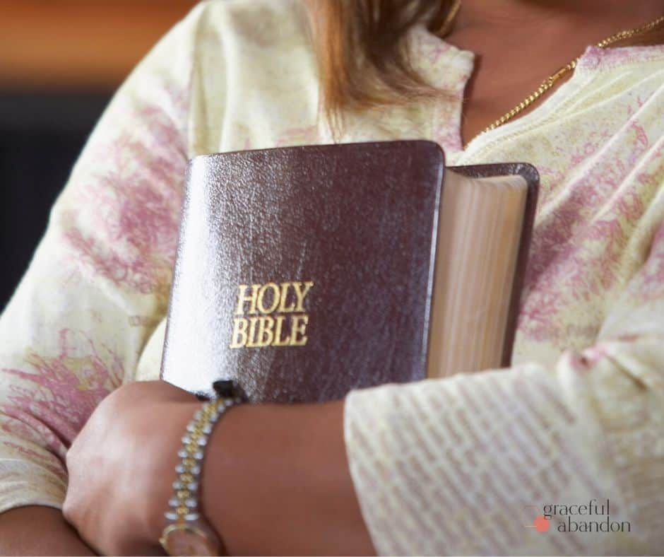 woman hugging bible/ holding fast to Scripture