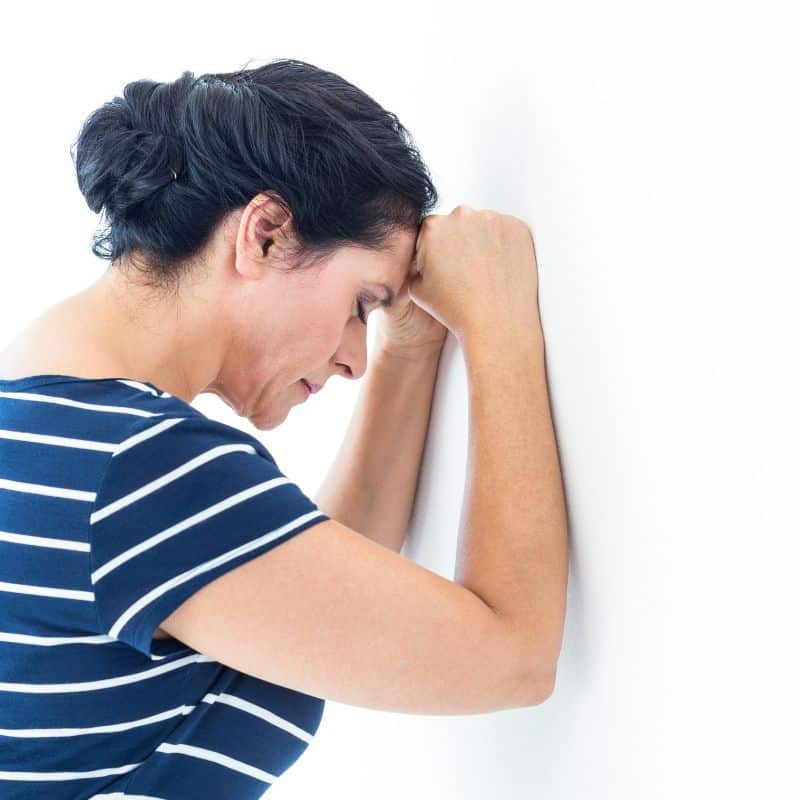 women leaning her head against the wall in frustration